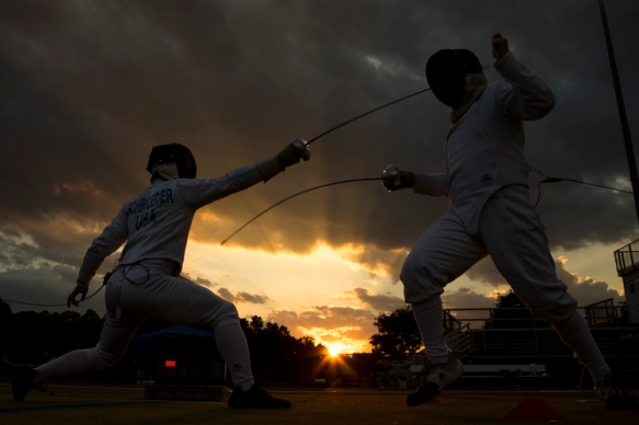 photo of two fencers against a stormy sky
